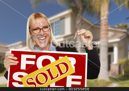 Excited Woman Holding House Keys and Sold Real Estate Sign stock photo, Excited Woman Holding House Keys and Sold Real Estate Sign in Front of Nice New Home. by Andy Dean