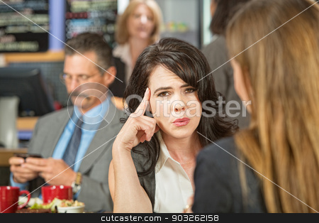 Woman with Finger on Head stock photo, Woman with finger on head and sitting with friend by Scott Griessel
