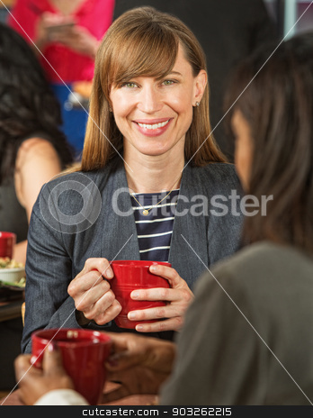 Pretty Woman in Cafe with Cup stock photo, Beautiful smiling businesswoman in coffee house with cup by Scott Griessel