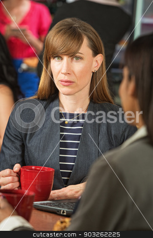 Serious Businesswoman in Cafe stock photo, Serious businesswoman with mug in coffee house by Scott Griessel