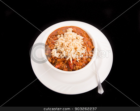 Bowl of Chili Over Rice on Black Background stock photo, A white bowl of chili con carne with beans served over rice on a black background by Darryl Brooks
