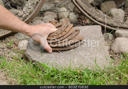 man hand put iron horseshoe pile on stone outdoor  stock photo, man hand put old rusty iron horseshoe pile on stone outdoor  by sauletas