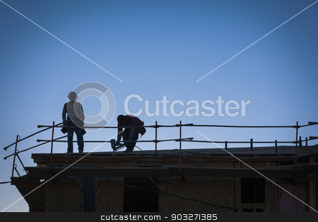 Construction Workers Silhouette on Roof stock photo, Construction Workers Silhouette on Roof of Building. by Andy Dean