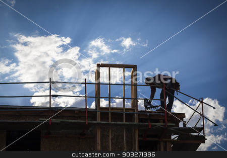 Construction Worker Silhouette on Roof stock photo, Construction Worker Silhouette on Roof of Building. by Andy Dean