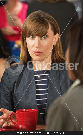 Wide Eyed Woman Listening stock photo, Surprised business woman with wide eyes listening to coworker by Scott Griessel