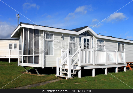 White caravan on a trailer park stock photo, Side view of a modern white caravan on a trailer park. by Martin Crowdy