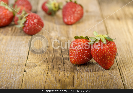 Fresh strawberries on wooden table stock photo, Fresh strawberries on wooden table. Focus on first two strawberries by manaemedia