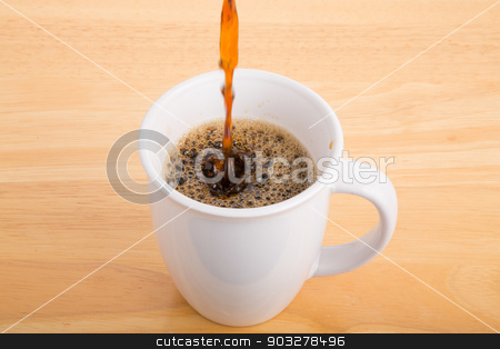 Pouring a Cup of Coffee stock photo, Pouring a cup of black coffee on a wood table by Darryl Brooks