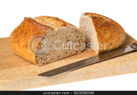 Artisan whole wheat bread on breadboard stock photo, Whole wheat or multi grain brown bread fresh from oven bakery placed on wooden breadboard with knife and isolated against a white background by Steven Heap