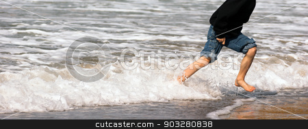 Young Boy Running Feet Ocean Beach Surf Crashing Sea Foam stock photo, Panoramic shot of boy playing in the ocean surf by Christopher Boswell