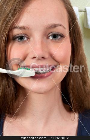 Beautiful Teenage Woman Brushing Teeth stock photo, Beautiful teenage woman practicing good oral dental care by brushing her teeth by Robert Byron