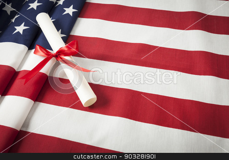 Ribbon Wrapped Diploma Resting on American Flag with Copy Space stock photo, Red Ribbon Wrapped Diploma Resting on American Flag with Copy Space. by Andy Dean