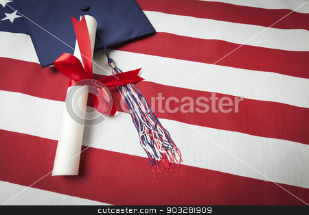 Graduation Cap and Diploma Resting on American Flag stock photo, Graduation Cap with Tassel and Red Ribbon Wrapped Diploma Resting on American Flag. by Andy Dean