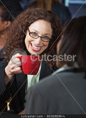 Happy Woman Laughing stock photo, Happy woman laughing with coworker in cafeteria by Scott Griessel