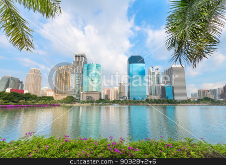 Tropical modern city with palm trees and lake on front stock photo, Modern city skyline of business district downtown with tropical palm tree  and blue lake on front in day under blue sky by Iryna Rasko