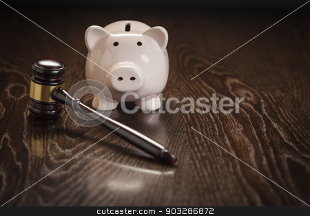 Gavel and Piggy Bank on Table stock photo, Gavel and Piggy Bank on Wooden Table. by Andy Dean