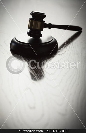 Dramatic Gavel Silhouette on Reflective Wood stock photo, Dramatic Gavel Silhouette on Reflective Wood Surface. by Andy Dean