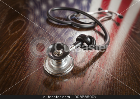 Knotted Stethoscope with American Flag Reflection on Table stock photo, Knotted Stethoscope with American Flag Reflection on Wooden Table. by Andy Dean