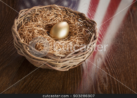Golden Egg in Nest with American Flag Reflection on Table stock photo, Golden Egg in Nest with American Flag Reflection on Wooden Table. by Andy Dean