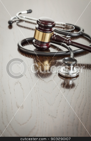 Gavel and Stethoscope on Reflective Table stock photo, Gavel and Stethoscope on Reflective Wooden Table. by Andy Dean
