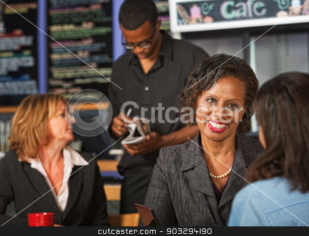 Cheerful Woman in Cafe stock photo, Cheerful adult female with friend in coffee house by Scott Griessel