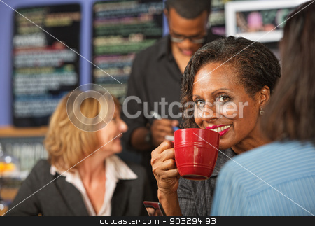 Woman Sipping Coffee stock photo, Cheerful business woman sipping beverage in cafe by Scott Griessel
