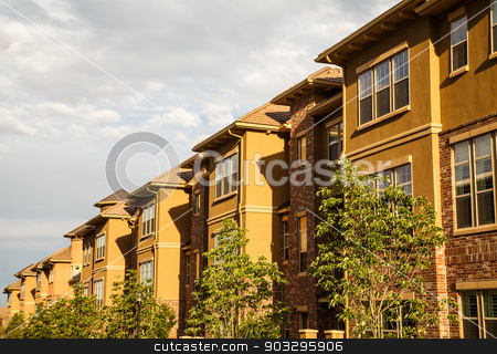 Row of Brick and Stucco Condos in Morning Light stock photo, Modern Stucco and Brick Condos Under Summer Sky by Darryl Brooks