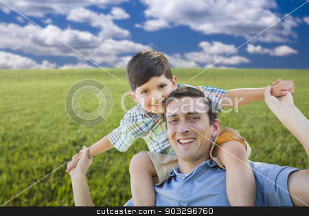 Mixed Race Father and Son Playing Piggyback on Grass Field stock photo, Happy Mixed Race Father and Son Playing Piggyback on Grass Field. by Andy Dean