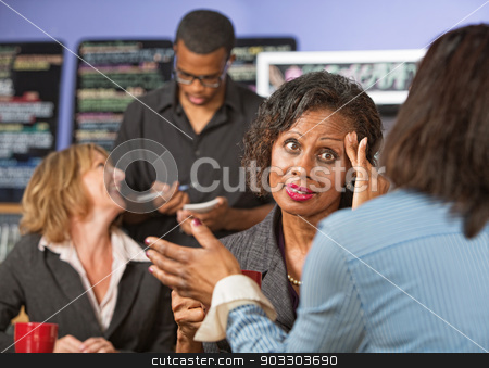 Lady with Headache Listening stock photo, Woman with fingers on head listening to friend in cafe by Scott Griessel