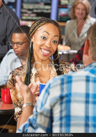 Young Woman Talking with Friend stock photo, Cheerful beautiful young woman with braids talking with friend by Scott Griessel