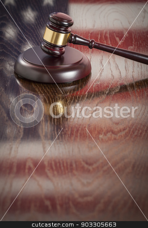 Wooden Gavel Resting on Flag Reflecting Table stock photo, Wooden Gavel Resting on American Flag Reflecting Table. by Andy Dean