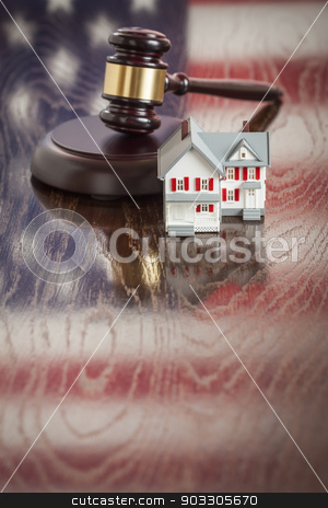 Small House and Gavel on Table with American Flag Reflection stock photo, Small House and Gavel on Wooden Table with American Flag Reflection. by Andy Dean