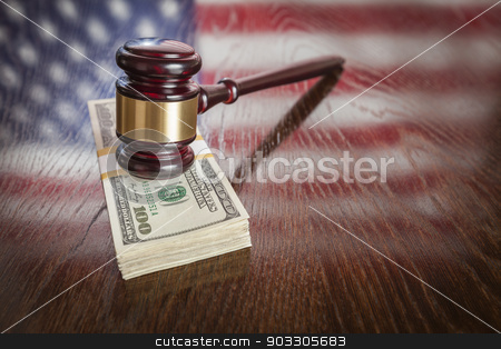 Wooden Gavel Resting on Money with American Flag Reflection stock photo, Wooden Gavel Resting on Stack of Money with American Flag Reflection on Table. by Andy Dean