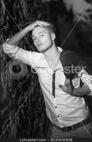 Handsome blond young man against stone wall at night stock photo, Handsome blond young man leaning against stone wall at night, black and white shot by Stefano Cavoretto