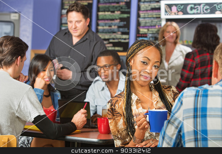 Cute Woman with Braids in Cafe stock photo, Beautiful grinning young Hispanic woman with long braids by Scott Griessel