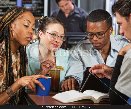 Students Studying stock photo, Cute group of four diverse students at table with book by Scott Griessel