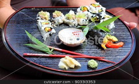 Sushi stock photo, Nicely decorated presentation of sushi on a black serving plate. by Henrik Lehnerer