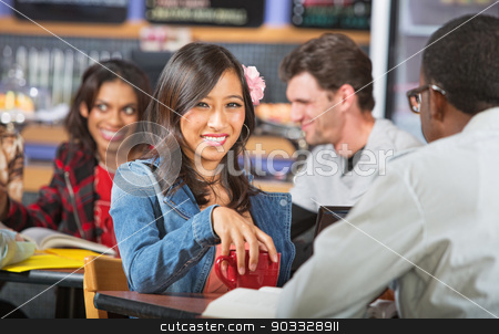 Smiling Young Woman in Cafe stock photo, Smiling young Asian woman with coffee mug and friend by Scott Griessel