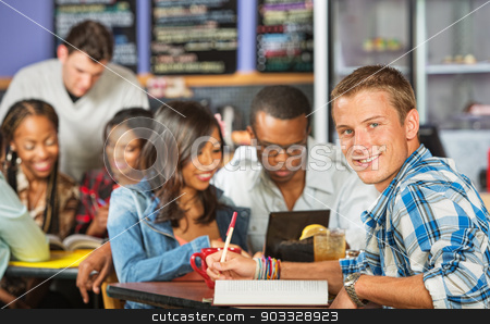 Smiling Student Doing Homework stock photo, Handsome male student with friends in coffee house by Scott Griessel