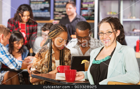 Cheerful Female Student stock photo, Happy young woman with students in coffee house by Scott Griessel