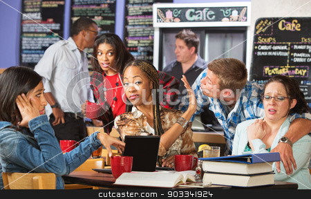 Man Trying to Kiss Women stock photo, Cringing women annoyed with man kissing them in cafe by Scott Griessel