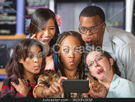 Cute Group Making Faces stock photo, Group of young students making faces on phone by Scott Griessel