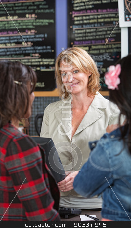 Cheerful Restaurant Manager stock photo, Cheerful restaurant owner at counter with customers by Scott Griessel