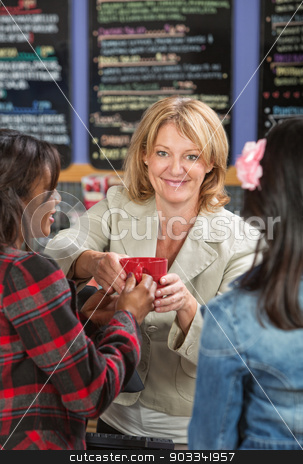 Cashier Serving Drinks stock photo, Smiling restaurant cashier serving drinks to customers by Scott Griessel