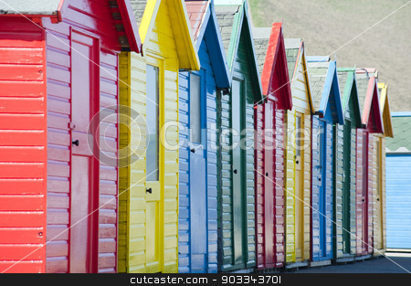 Row of colorful wooden beach huts stock photo, Row of colorful traditional wooden beach huts overlooking the Whitby Sands beach, Whitby, North Yorkshire, close up view receding from the camera by Stephen Gibson