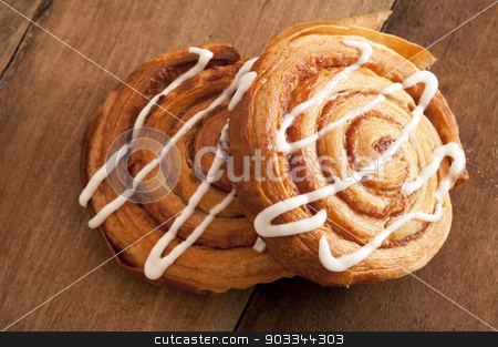 Freshly baked flaky Danish pastries stock photo, Freshly baked spiral Danish pastries with flaky puff pastry filled with apple or almond paste and drizzled with white icing for a delicious sticky sweet snack or dessert by Stephen Gibson