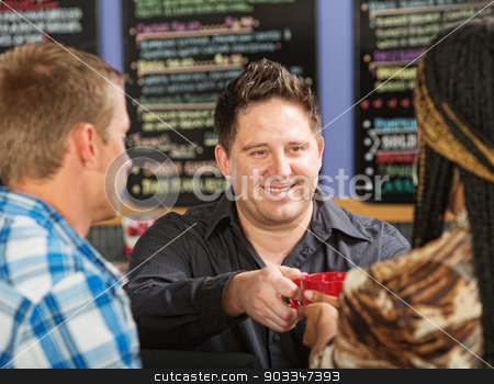 Happy Worker Serving Drinks stock photo, Smiling Hispanic coffee house owner serving beverage by Scott Griessel