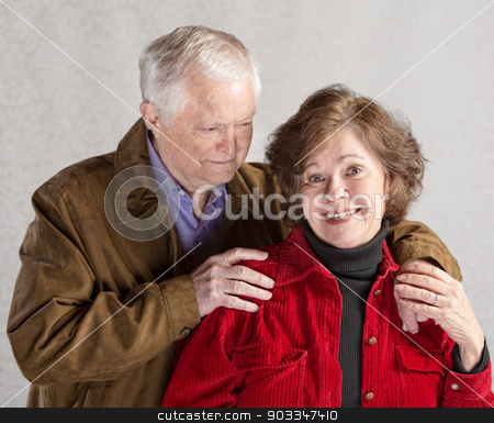 Cute Couple Hugging stock photo, Cute mature couple hugging over gray background by Scott Griessel