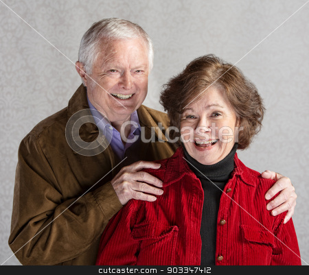 Laughing Senior Couple stock photo, Elderly Caucasian couple laughing in front of gray background by Scott Griessel