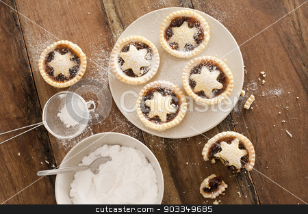 Baking Christmas mince pies stock photo, Baking a plate of tasty traditional Christmas mince pies with decorative pastry stars sprinkled with icing sugar, view from above on a wooden kitchen counter by Stephen Gibson